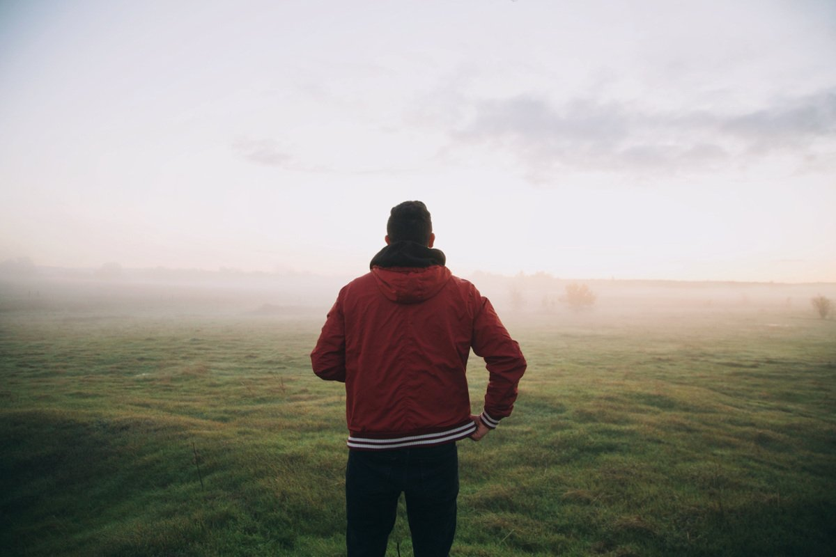 guy in red coat looking out into a field